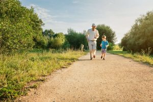 Grandfather and grandson walk on a path together
