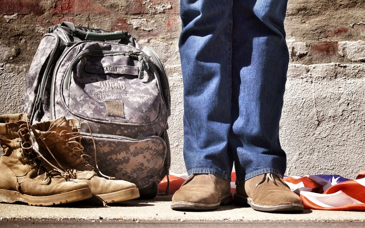 Veteran with boots, flag, and bag